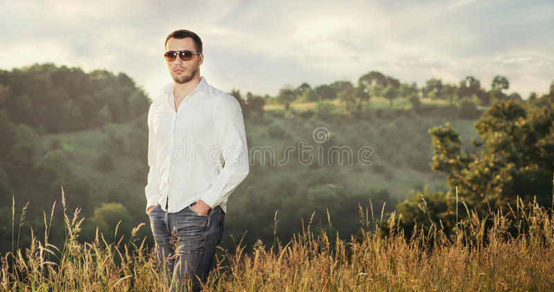 Gorgeous young man. Handsome young man with sunglasses posing against natural background, outdoors. Copy space. Gorgeous guy royalty free stock image