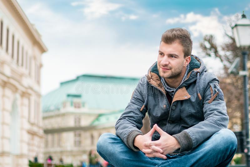 Gorgeous young man posing in front of old buildings stock images