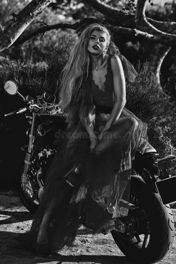 Beautiful woman wearing dress posing seated on motorcycle black and white image stock image