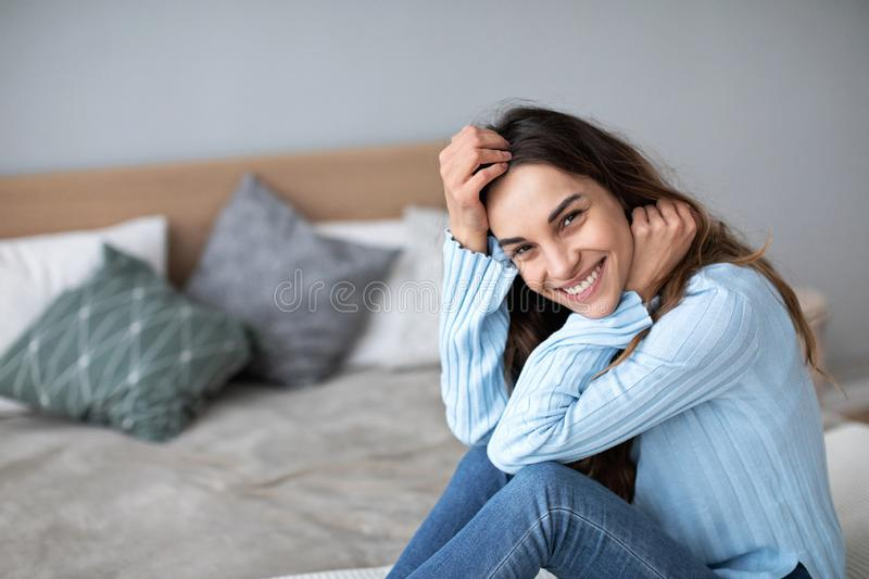 Gorgeous young smiling woman is sitting on the couch and looks on camera stock photo