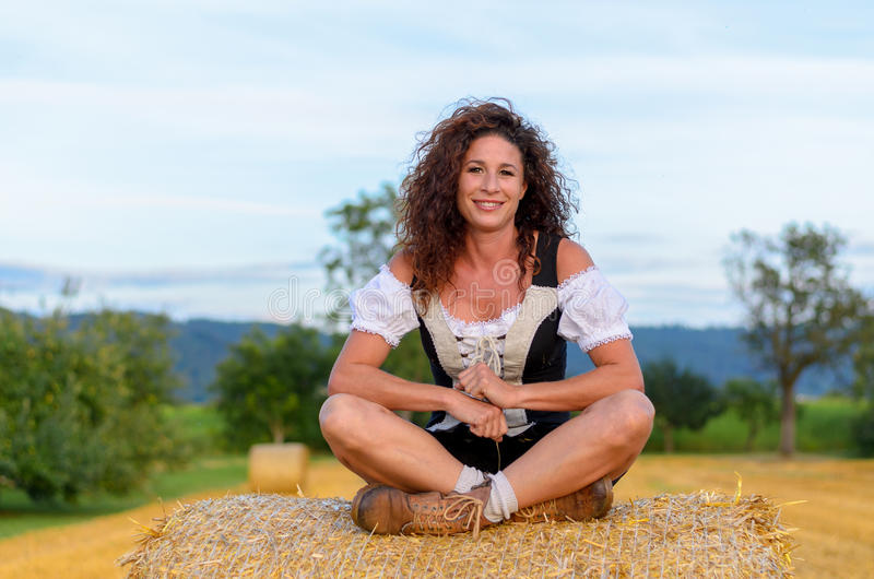 Gorgeous young woman in Bavarian clothing. Sitting cross-legged on a round hay bale in an agricultural field smiling at the camera stock photography