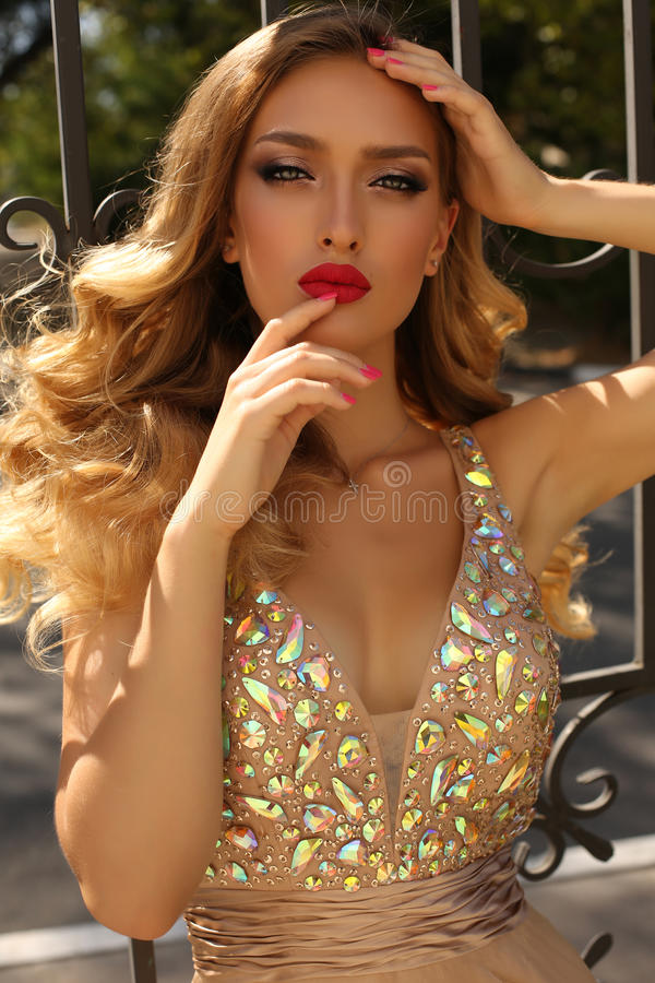 Gorgeous young woman with blond curly hair in luxurious dress royalty free stock images