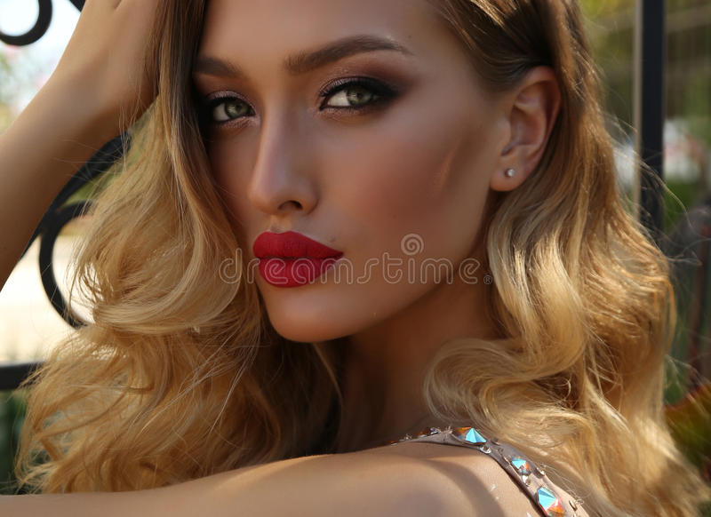 Gorgeous young woman with blond curly hair in luxurious dress. Fashion photo of gorgeous young woman with blond curly hair and bright makeup, in luxurious sequin stock photo