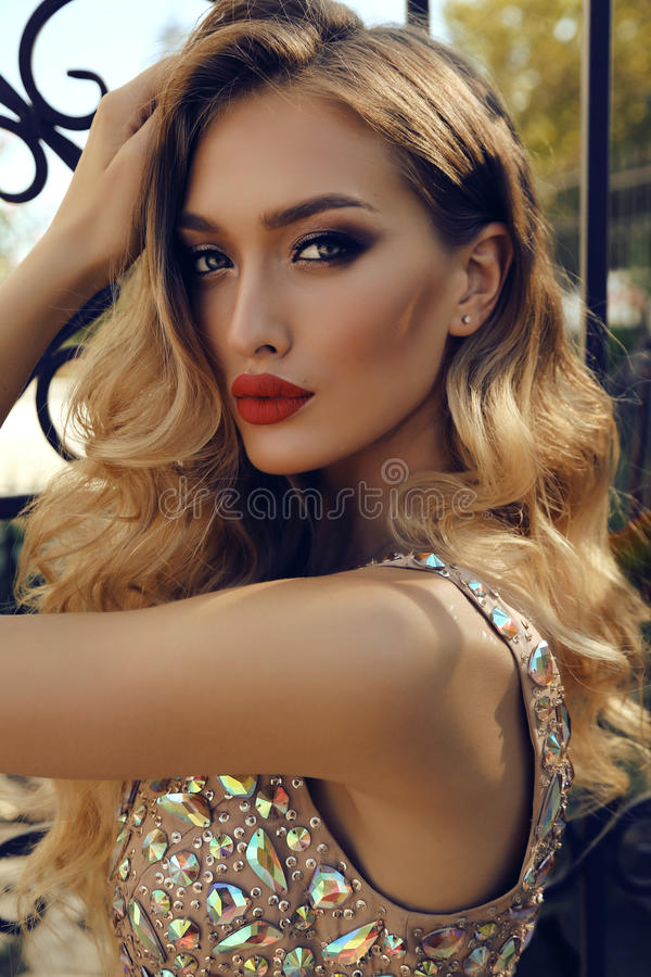Gorgeous young woman with blond curly hair in luxurious dress. Fashion photo of gorgeous young woman with blond curly hair and bright makeup, in luxurious sequin royalty free stock images
