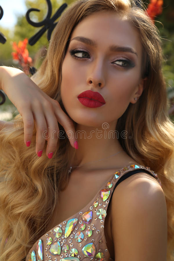 Gorgeous young woman with blond curly hair in luxurious dress. Fashion photo of gorgeous young woman with blond curly hair and bright makeup, in luxurious sequin stock photos
