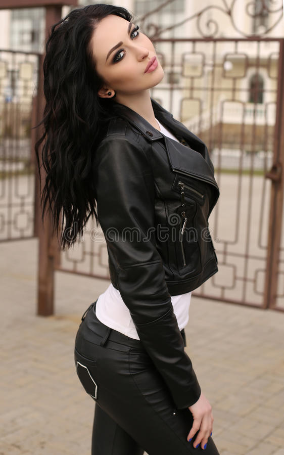 Gorgeous young woman with dark hair in casual clothes, leather j royalty free stock images