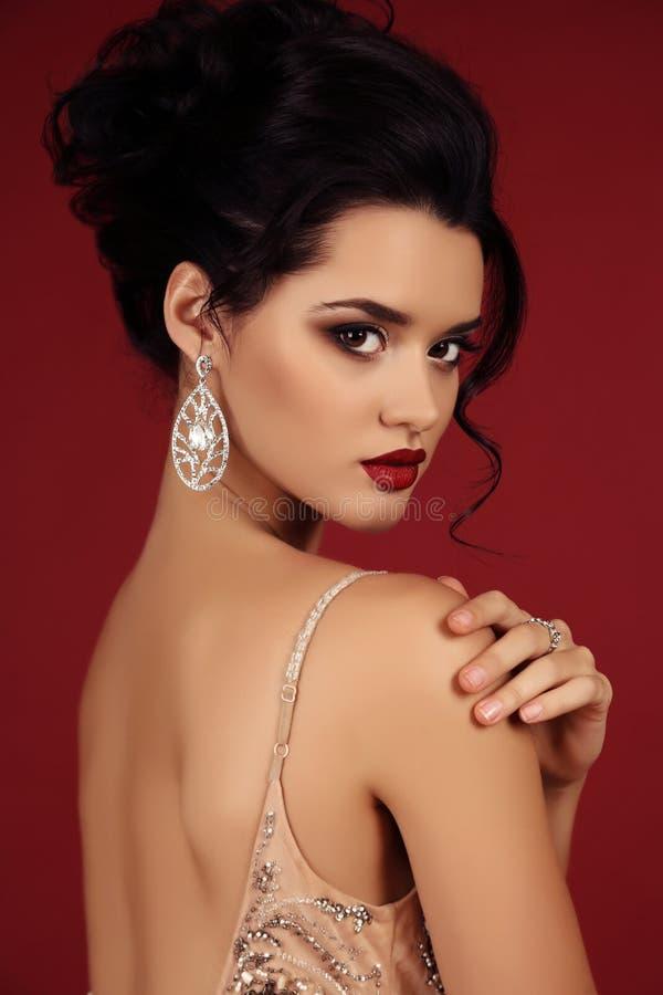 Gorgeous young woman with dark hair in luxurious dress. Fashion studio photo of gorgeous woman with dark hair wears luxurious sequin dress and precious bijou stock images