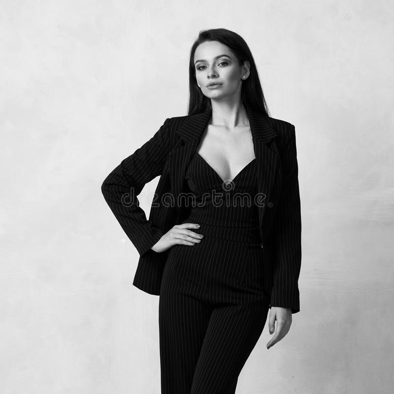 Beautiful brunette girl in black striped jumpsuit and blazer stock photo