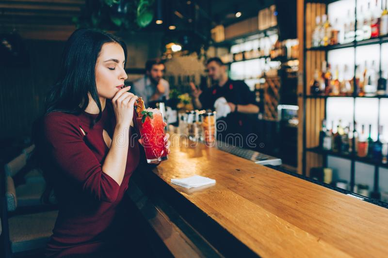 Gorgeous young woman is drinking her cocktail at the barman`s stand. She is enjoying that. Both barman and another guy. Gorgeous young women is drinking her royalty free stock photo