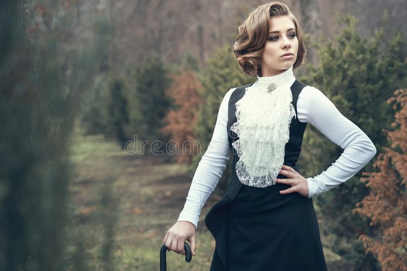 Gorgeous young woman with elegant Victorian hairstyle walking in the misty autumn park stock photos