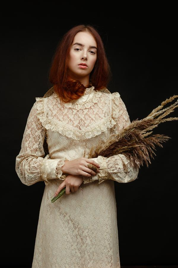 Woman holding dry reed. Gorgeous young woman holding dry reed and posing among the dry reed royalty free stock photography