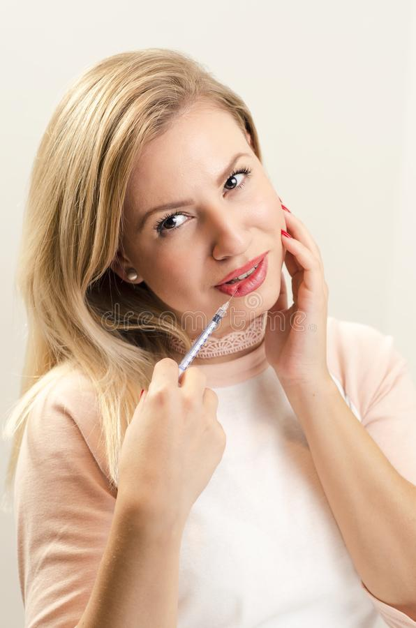 Gorgeous young woman holding syringe on her lip royalty free stock image