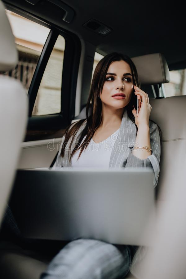 Young woman with laptop sitting in car and talking on the phone royalty free stock images