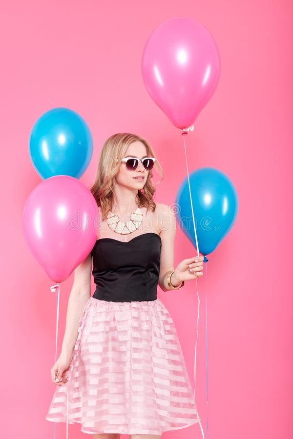 Gorgeous young woman in party outfit holding bunch of colourful balloons, isolated over pastel pink background. Birthday Party. Gorgeous young woman in party royalty free stock photos