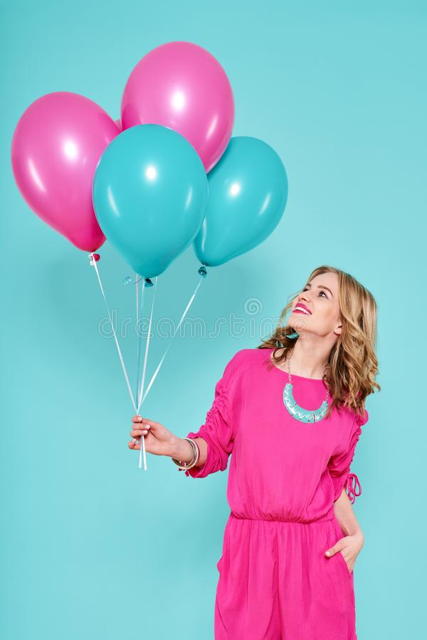 Gorgeous young woman in party summer dress holding bunch of colourful balloons, isolated over pastel blue colored background. Birthday Party concept stock photo