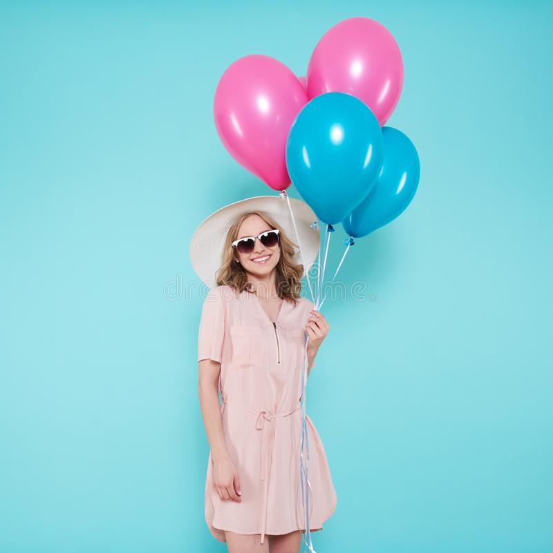 Gorgeous young woman in party summer dress and straw hat holding bunch of colourful balloons, isolated over pastel blue. Gorgeous young woman in party summer stock images