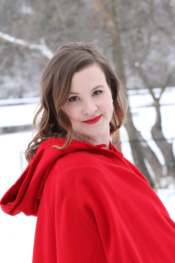 Beautiful curly, long haired woman in vintage red cape riverside in winter royalty free stock image