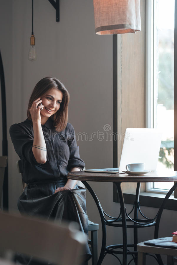 Gorgeous young woman talking by phone. Look at laptop. royalty free stock images