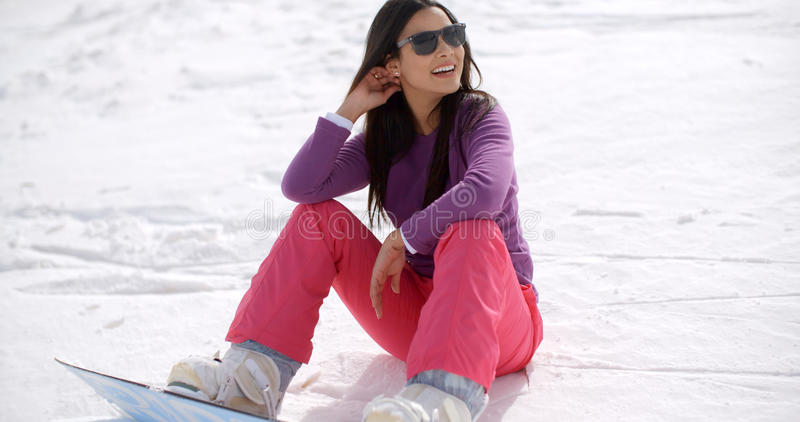 Gorgeous young woman using a snowboard stock image