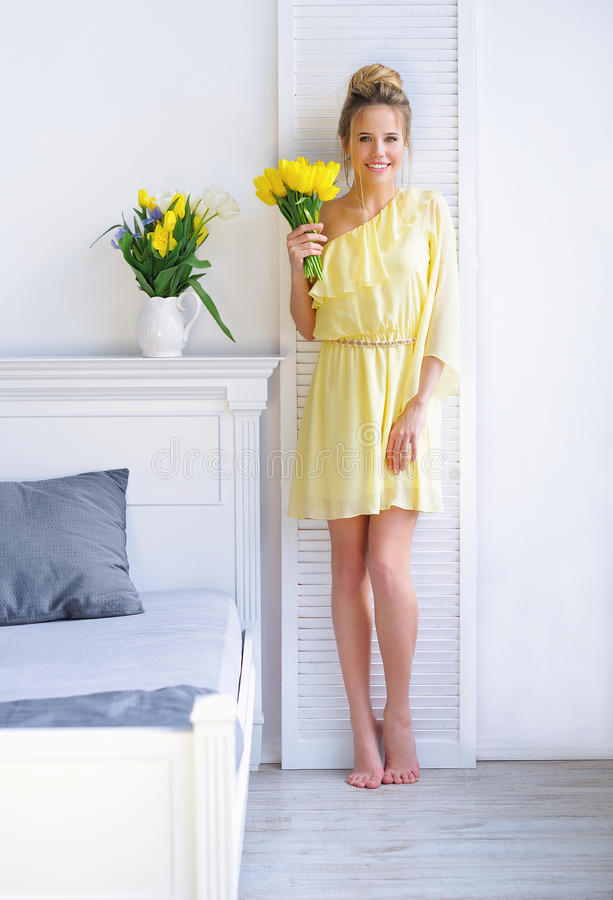 Gorgeous young woman with yellow tulips stock image