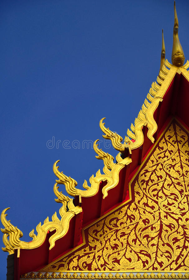 Gorgeously crafted golden gable. Soars into blue sky at Thai temple Wat Pasuk Maneechak in Nonthaburi province of Thailand royalty free stock photos