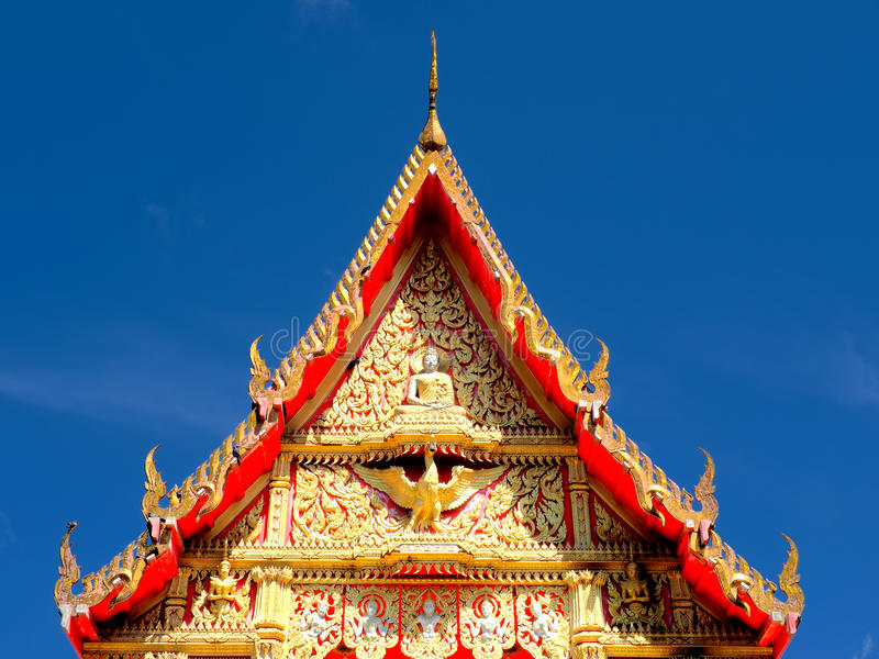 Gorgeously crafted temple gable. Featuring meditating Buddha soars into blue sky at Wat Rat Niyom in Nonthaburi province of Thailand royalty free stock photography