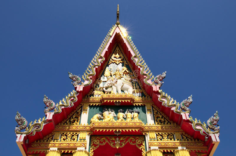 Gorgeously crafted temple gable. Gorgeously crafted golden gable soars into blue sky at Thai temple Wat Phlap in Nakhon Ratchasima province of Thailand stock photography