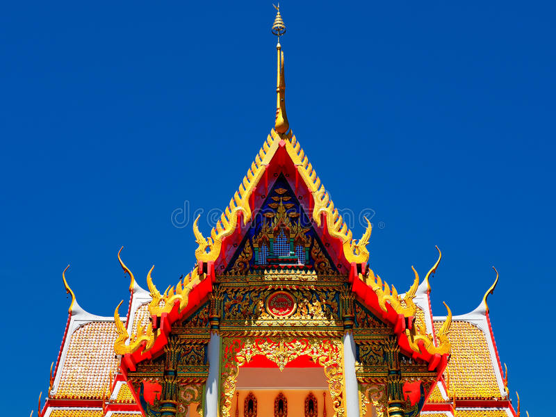 Gorgeously crafted temple gable. Gorgeously crafted golden gable soars into blue sky at Thai temple Wat Pho Koy in Suphan Buri province of Thailand stock photos