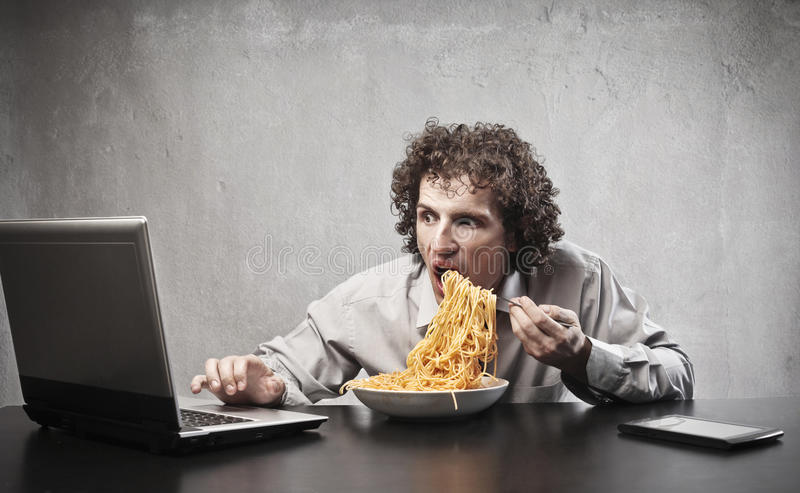 Gorging Businessman. Businessman gorging of red spaghetti while using a laptop computer royalty free stock photo