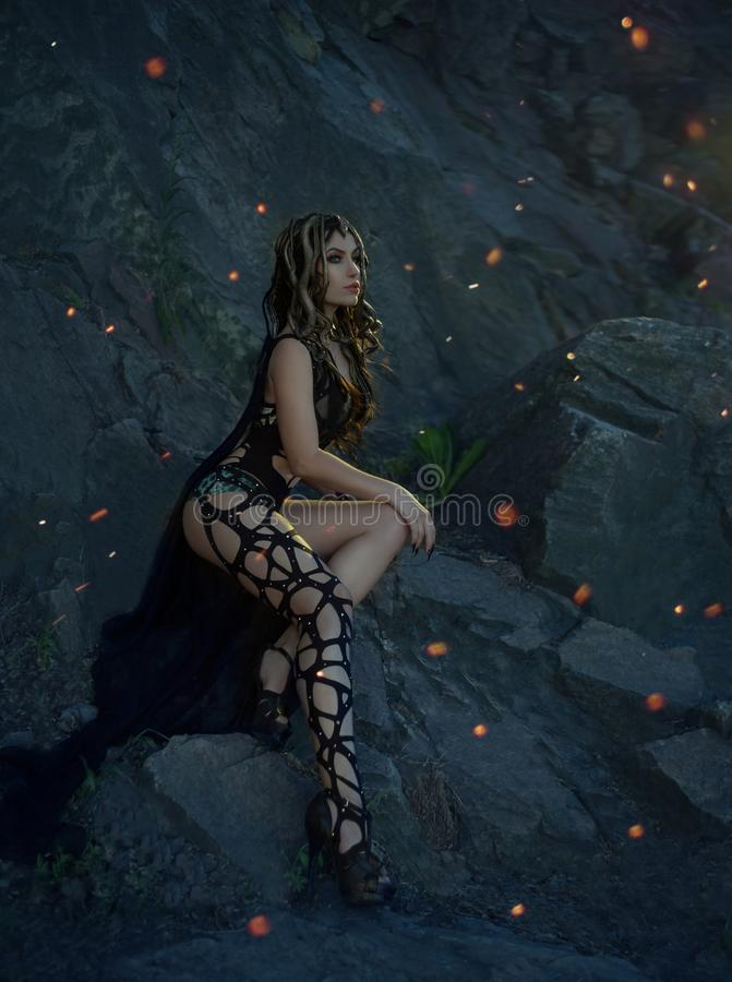 Gorgon水母、辫子头发和金子的图象曲折前进 女孩在晚上摆在反对岩石的背景火热 免版税库存照片