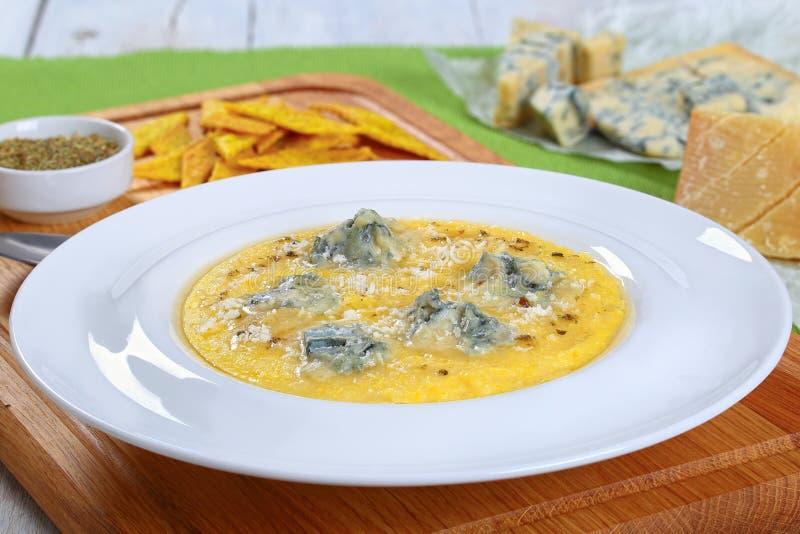 Gorgonzola polenta som strilas med parmesan, närbild arkivfoton
