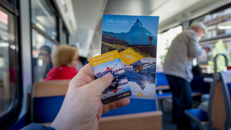 Gornergrat booklet and ticket in hand in the Red train climbing up to Gornergrat station on Z. ZERMATT, SWITZERLAND - May 16. 2017: Gornergrat booklet and ticket royalty free stock images