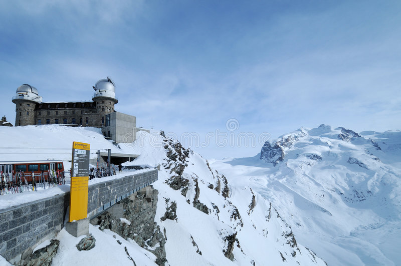 Gornergrat observatory. Snowy landscape of Gornergrat ridge and glacier with Kolner observatory in foreground, Pennine Alps, Switzerland royalty free stock images