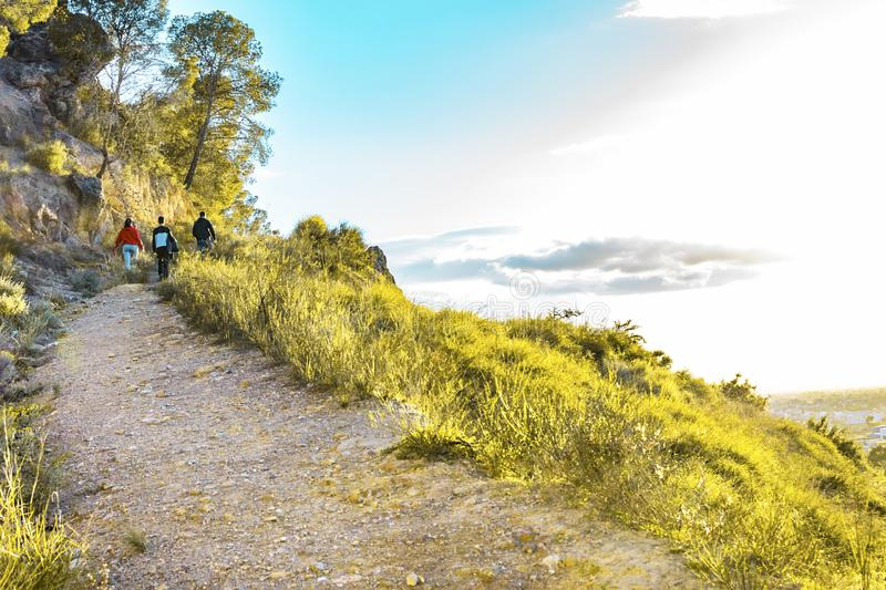 Gorup de los amigos que caminan en montañas en la puesta del sol foto de archivo libre de regalías