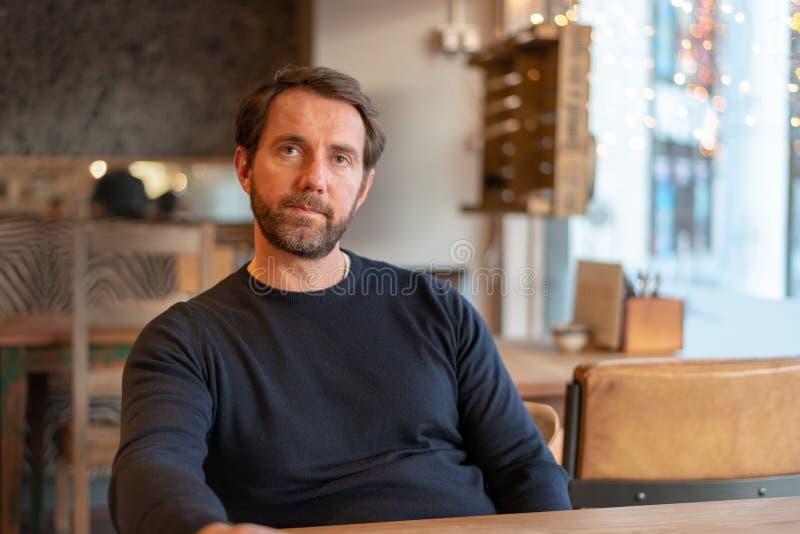 Gorzki i rozczarowywający w średnim wieku caucasian męski obsiadanie przy stołem w sklepie z kawą obrazy royalty free