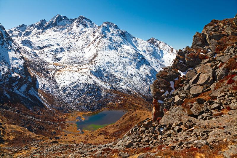 Gosainkunda-Gebirgssee unter schneebedeckten Bergen lizenzfreie stockbilder