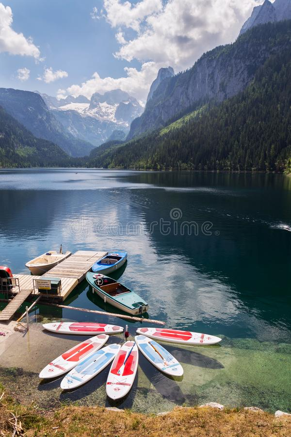 Paddle surf lying on surface of Vorderer Gosausee lake near bank in Gosau, Austria stock images