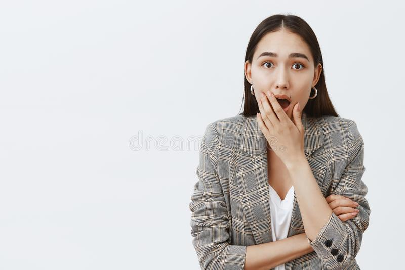 Gosh, оно истинный Крытая съемка сотрясенной и возбужденной привлекательной темн-с волосами женщины в ультрамодной куртке, падая  стоковые фото