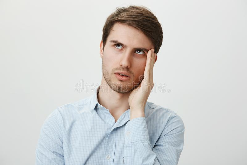 Gosh, so annoying, hope she would not talk to me. Portrait of bothered handsome young man in casual shirt holding palm. Near cheek to hide face from clingy ex royalty free stock photography