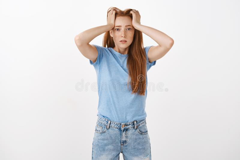 Gosh hate being student. Portrait of cute redhead woman under pressure holding hands on head with perplexed and troubled. Look being tired and fed up of paper royalty free stock image