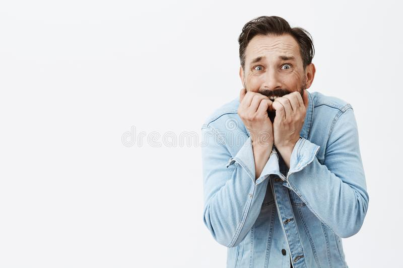 Gosh not again, most scary fear come alive. Portrait of shook and terrifying anxious guy, biting fingernails and. Stooping while standing over gray background royalty free stock photography