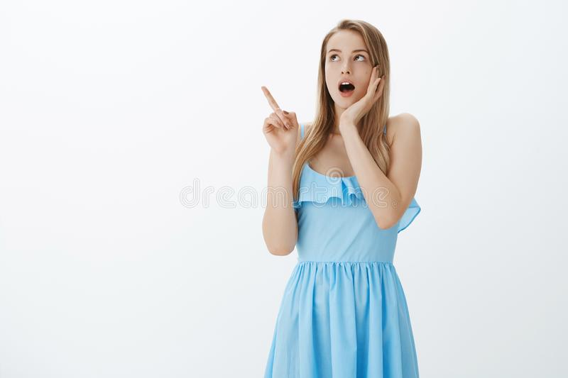 Gosh what it is. Portrait of stunned shocked and speechless attractive young blond girl in blue dress dropping jaw royalty free stock photos
