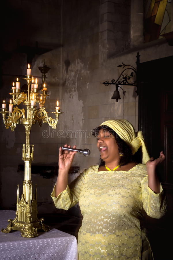 Gospel songs for the Lord. Gospel singer in a dark medieval church with 17th century interior stock image