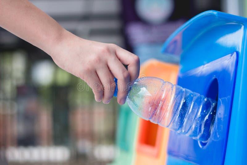 Gospodarka odpadami, kobiety miotania plastikowa butelka w przetwarza kosz Jałowy separacyjny grat dla różnych banialuk przed kro obraz stock
