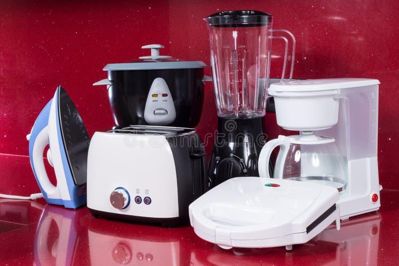 Gospodarstw domowych urządzenia w nowożytnym kuchennym czerwonym tle zdjęcie stock