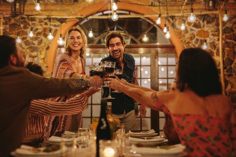 Gospodarz para wznosi toast napoje z gościem przy przyjęciem zdjęcia royalty free