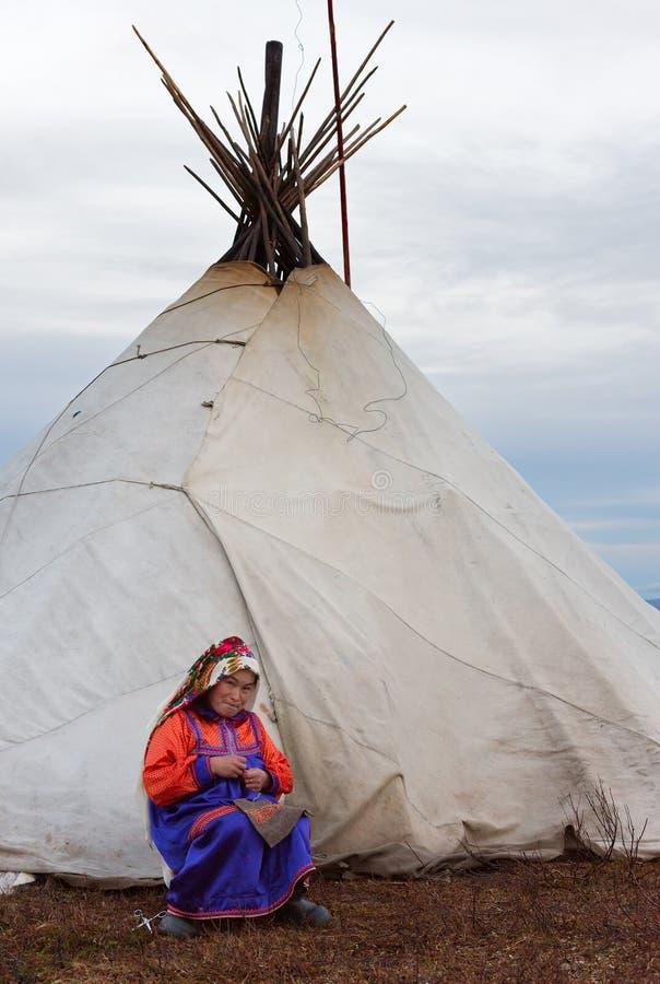 Gospodyni domowa nenets koczownika plemię w krajowym kostiumu naprawia ubrania przed rodzinnym kmotrem podczas jesień renifera mi fotografia royalty free