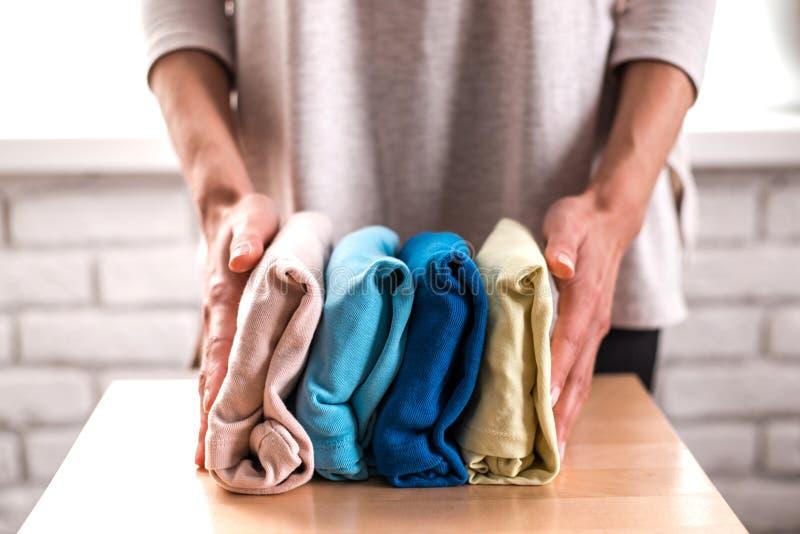 Gospodyni domowa starannie składa stertę odziewa obrazy stock