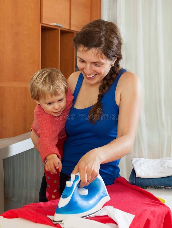 Gospodyni domowa z dziecka prasowaniem odziewa obraz stock