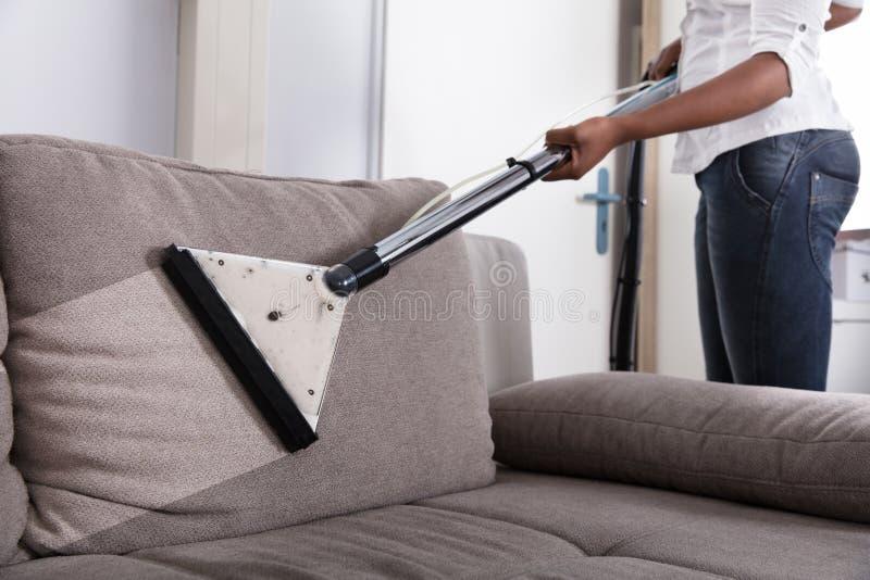 Gospodyni domowej Cleaning kanapa Z Próżniowym Cleaner obraz stock